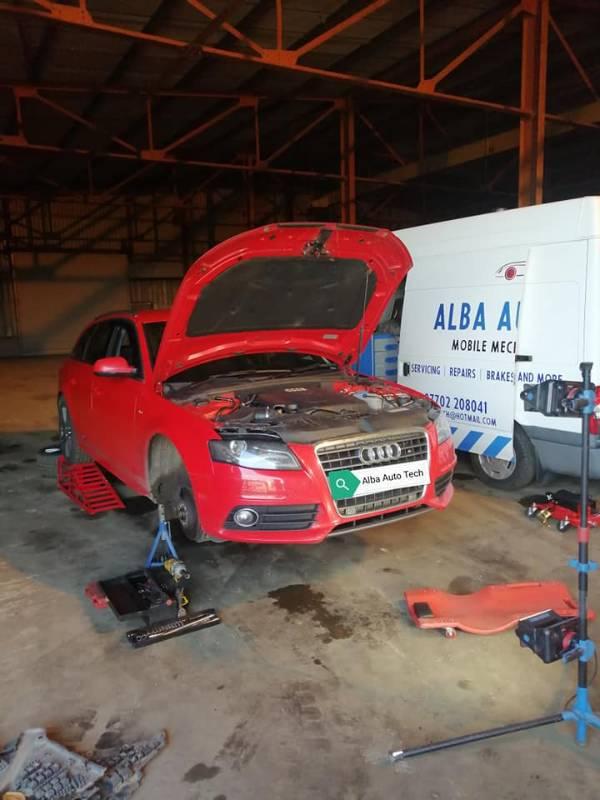 Audi A4 with bonnet open next to repair van